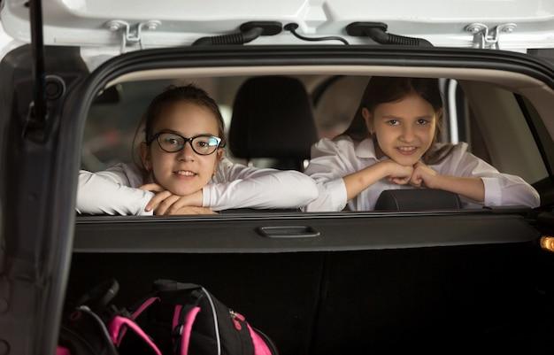 Portret van twee vrolijke meisjes die in de auto zitten en door de achterkant kijken