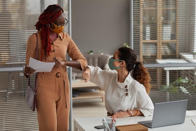 Portret van twee vrolijke onderneemsters die maskers in bureau dragen en ellebogen stoten als contactloze groet