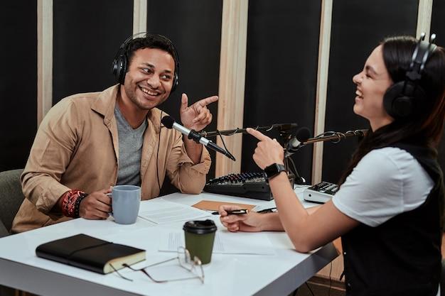 Portret van twee vrolijke radiopresentatoren man en vrouw die lachend naar elkaar wijzen terwijl ze een