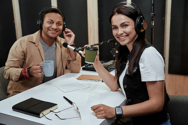 Portret van twee vrolijke radiopresentatoren, man en vrouw die naar de camera glimlachen en koffie of thee drinken terwijl