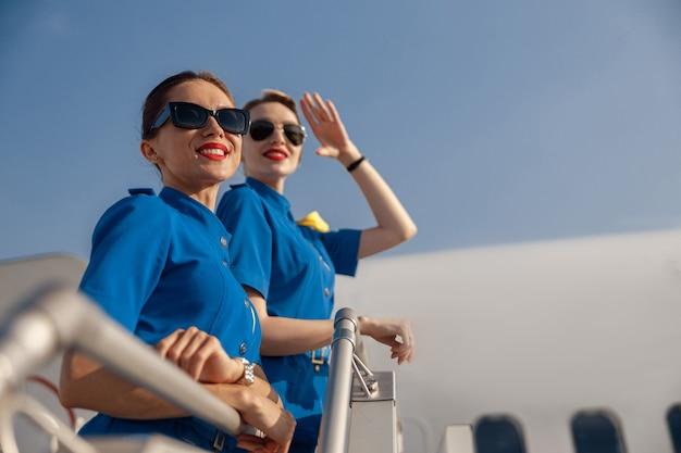 Portret van twee vrolijke stewardessen in blauw uniform en zonnebril die weg glimlachen, samen op een zonnige dag op de airstair staan. vliegtuigbemanning, bezettingsconcept