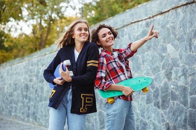 Portret van twee vrolijke tieners die skateboards houden