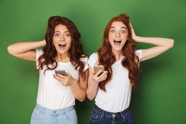 Portret van twee vrolijke vrouwen met gemberhaar die camera bekijken en mobiele telefoons houden, die over groene achtergrond worden geïsoleerd