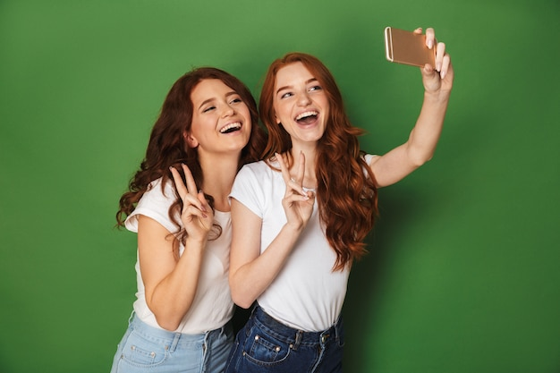 Portret van twee vrolijke vrouwen met gemberhaar die selfie op smartphone nemen en overwinningsteken tonen, dat over groene achtergrond wordt geïsoleerd