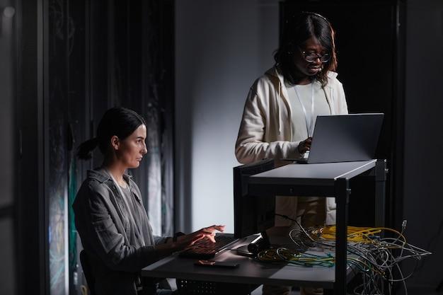 Portret van twee vrouwelijke netwerkingenieurs die een laptop gebruiken terwijl ze in een donkere serverruimte werken, kopieer ruimte