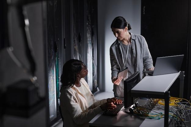 Portret van twee vrouwelijke netwerkingenieurs die een laptop gebruiken terwijl ze samenwerken in een donkere serverruimte, kopieer ruimte