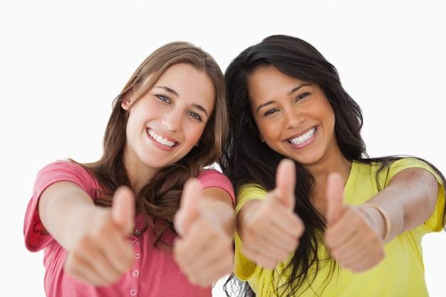 Portret van twee vrouwelijke studenten de thumbs-up