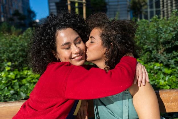 Portret van twee vrouwelijke vrienden bij zonsondergang - twee millennials, een blondine en een zwart meisje met afrohaar kijken naar de camera en knuffelen elkaar