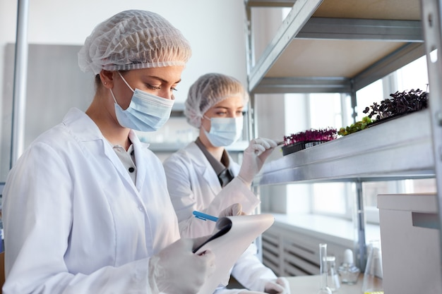 Portret van twee vrouwelijke wetenschappers plantmonsters te onderzoeken tijdens het werken in biotechnologie lab en schrijven op klembord, kopieer ruimte