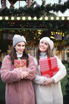 Portret van twee vrouwen met cadeautjes op kerstmarkt