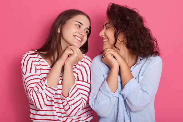 Portret van twee vrouwen poseren geïsoleerd over roze muur, schattige vrienden kijken naar elkaar met een charmante glimlach
