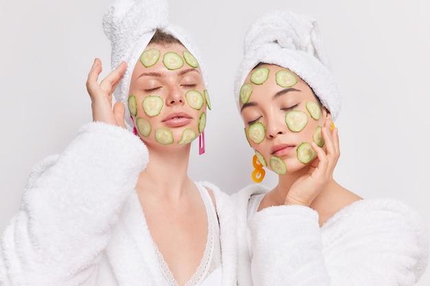 Portret van twee vrouwen van gemengd ras die met gesloten ogen staan en plakjes komkommer op het gezicht aanbrengen om te hydrateren en genieten van de zachtheid van de huid