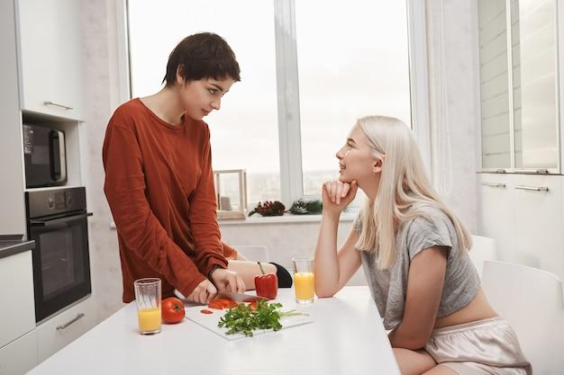 Portret van twee vrouwenzitting in keuken, drinkend sap en het maken van salade terwijl het spreken en het maken van grappen in ochtend. blond meisje flirt met haar vriendin terwijl ze ontbijt kookt
