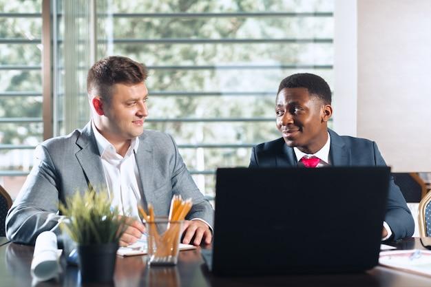 Portret van twee zakelijke partners zitten aan een tafel samen en werken.