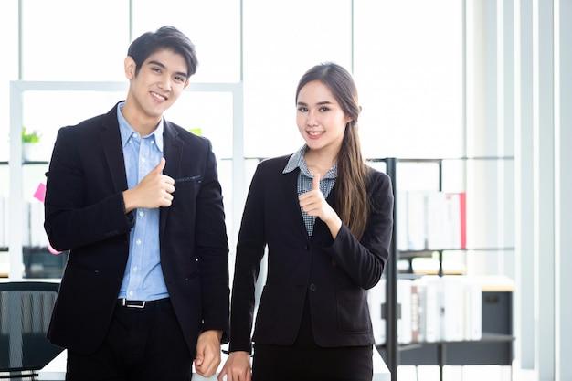 Portret van twee zakenman en onderneemsterpartners die positieve volwassen zaken bespreken die duimen en ideeën tonen op vergadering in bureau