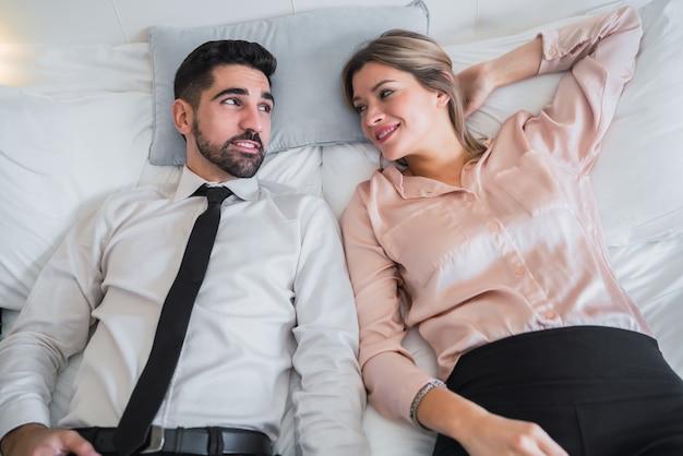 Portret van twee zakenmensen die een pauze nemen van het werk en op bed in de hotelkamer liggen. zakelijke reizen concept.