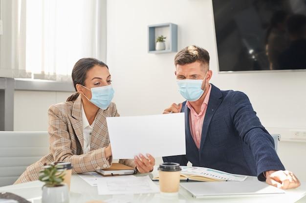Portret van twee zakenmensen man en vrouw dragen van maskers kijken naar documenten tijdens bijeenkomst op post pandemie kantoor