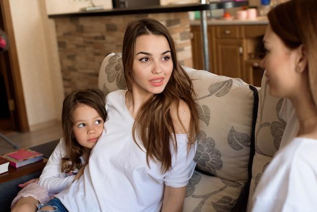 Portret van twee zussen en een klein meisje, zittend op de bank