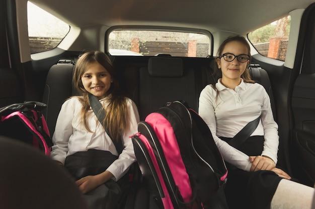 Portret van twee zussen glimlachend zittend op de achterbank van de auto met schooltassen