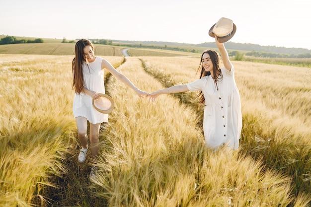 Portret van twee zussen in witte jurken met lang haar in een veld