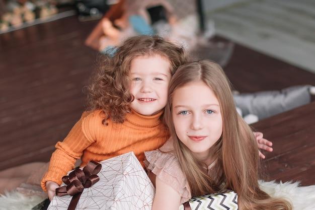 Portret van twee zussen op kerstavond. het concept van kerstmis