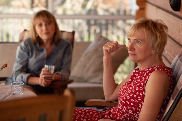 Portret van twee zussen vrouwen 55 jaar op patio houten huis