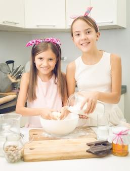 Portret van twee zusters die ingrediënten voor deeg in grote kom mengen