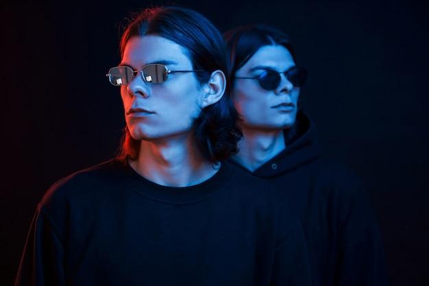 Portret van tweelingbroers. studio opname in donkere studio met neonlicht