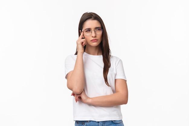 Portret van twijfelachtig aantrekkelijk donkerbruin meisje dat gefocust en verdacht kijkt