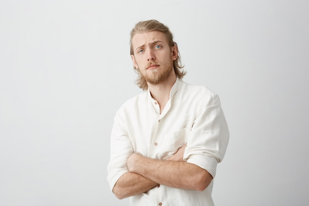 Portret van twijfelachtige aantrekkelijke blonde bebaarde man achteruit buigen, permanent met gekruiste handen, wenkbrauwen opheffen en kijken met ongeloof