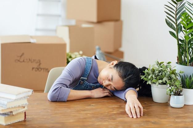 Portret van uitgeput aziatische vrouw slapen op houten tafel tijdens het inpakken voor verhuizing of verhuizing naar een nieuw huis