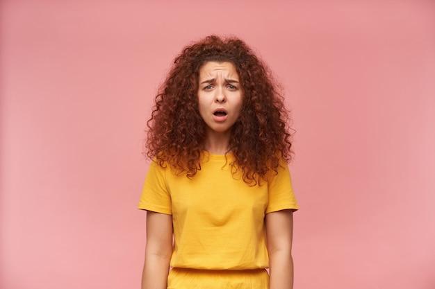 Portret van uitgeput, roodharig meisje met krullend haar dat gele t-shirt draagt