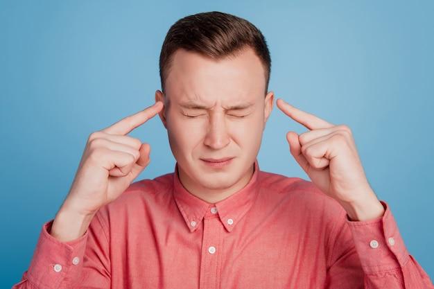 Portret van uitgeputte onwel man vingers hoofd lijden hoofdpijn pijn op blauwe achtergrond