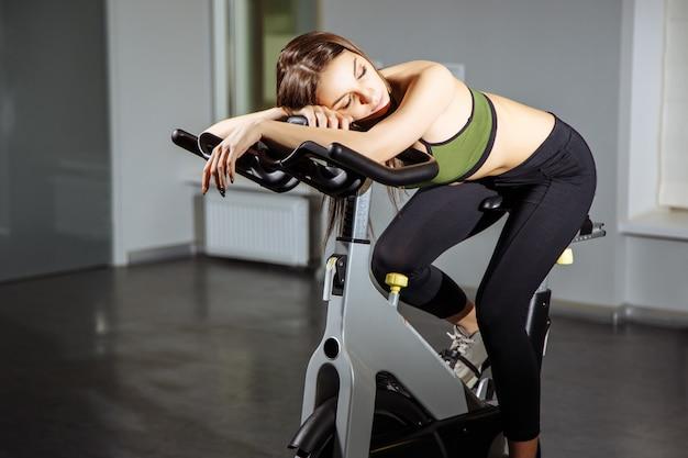 Portret van uitgeputte vrouw spinnende pedalen op hometrainer
