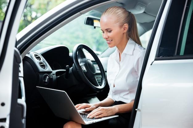 Portret van uitvoerende zakenvrouw die laptop gebruikt terwijl ze in de auto zit en werkt