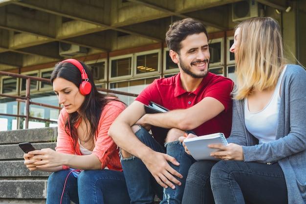 Portret van universiteitsstudenten die een pauze nemen en buiten ontspannen op de universiteitscampus. onderwijs concept.