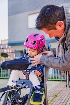 Portret van vader die de veiligheidshelm van de fiets sluit aan haar dochtertje dat in het fietsstoeltje zit. veilig en kinderbeschermingsconcept.