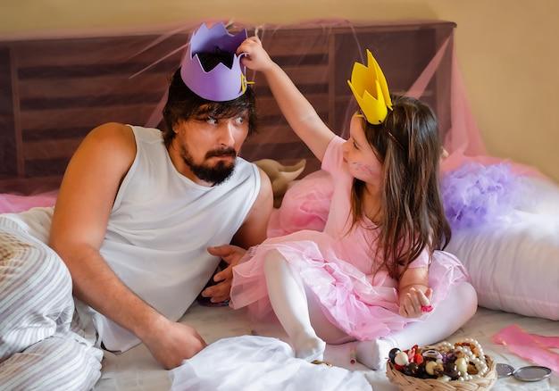 Portret van vader en dochter. de vader speelt met het meisje. kind zet de kroon op voor papa
