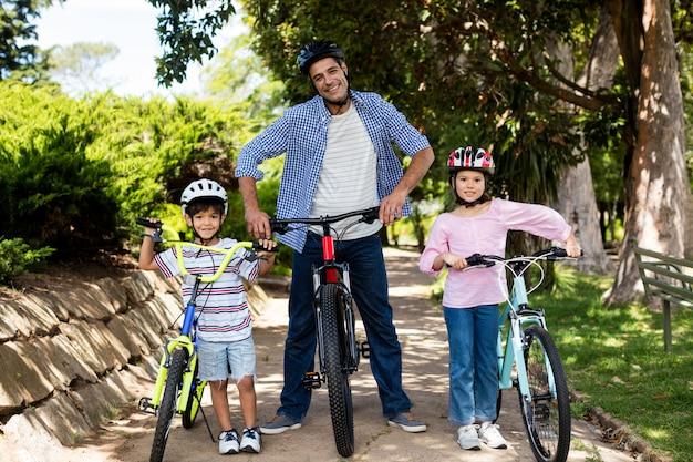 Portret van vader en kinderen die zich met fiets in park bevinden