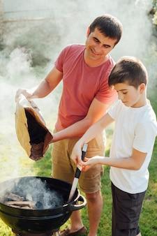 Portret van vader en zoon die de steenkolen in barbecue aansteken
