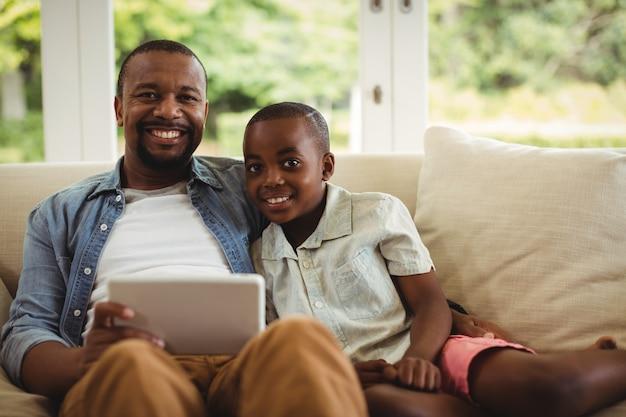 Portret van vader en zoon die laptop in woonkamer met behulp van