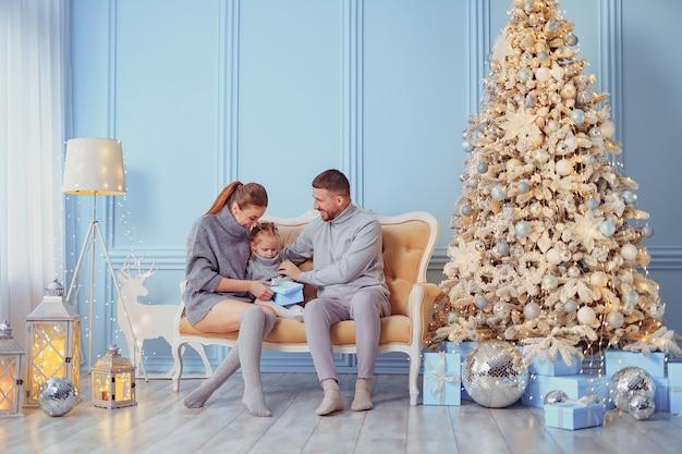 Portret van vader, moeder en dochter zittend op een bank thuis in de buurt van de kerstboom, allemaal zijn