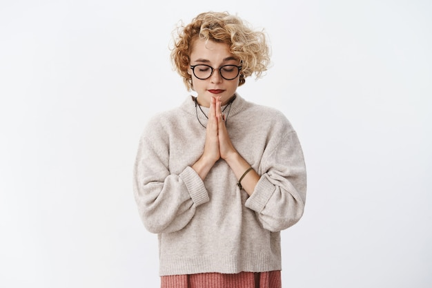 Portret van vastberaden aantrekkelijke stijlvolle hipster vrouw met kort krullend kapsel in bril en trui sluit ogen focus, hand in hand in bidden terwijl het maken van wens over witte muur