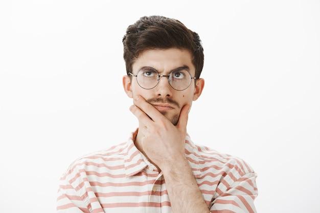 Portret van vastberaden, gefocuste en creatieve man met grappige snor, kin wrijven, opzoeken tijdens het denken, idee of concept verzinnen, hard wiskundig probleem proberen op te lossen, berekeningen maken