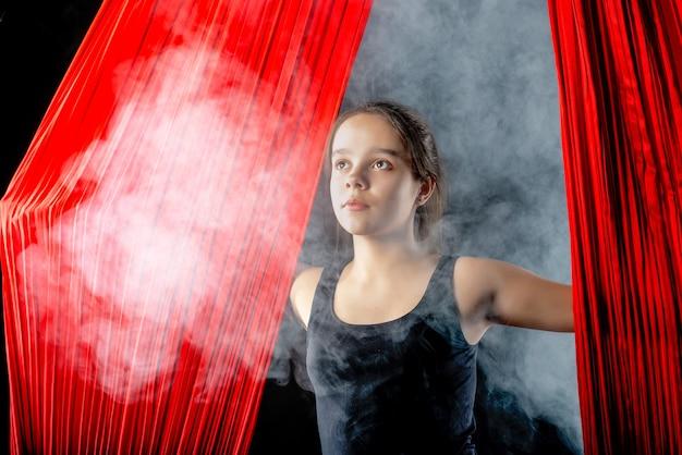 Portret van vastberaden vrij tienermeisje met luchtfoto rode linten op zwart omgeven door rook voor aanvang van gymnastiek show