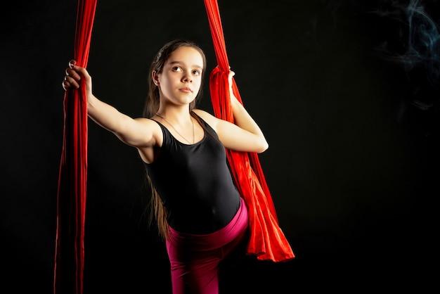 Portret van vastberaden vrij tienermeisje met luchtfoto rode linten op zwart voor aanvang van gymnastiek show