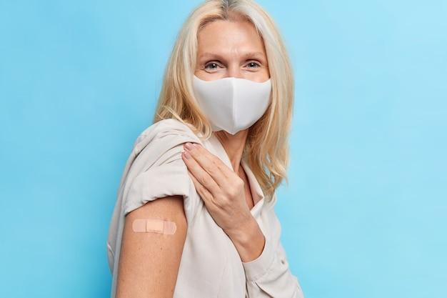 Portret van veertig jaar oude vrouw gevaccineerd tegen coronavirus toont arm na injectie draagt wegwerp beschermend masker poses tegen blauwe muur