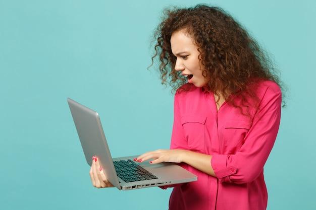 Portret van verbaasd afrikaans meisje in roze casual kleding met behulp van laptop pc-computer geïsoleerd op blauwe turquoise muur achtergrond in studio. mensen oprechte emoties, lifestyle concept. bespotten kopie ruimte.