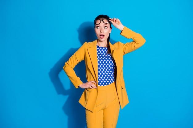 Portret van verbaasd bankier agent meisje touch bril kijken copyspace onder de indruk ongelooflijke onverwachte nieuwigheid geïsoleerd over blauwe kleur achtergrond