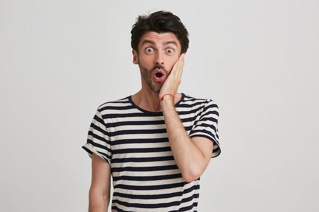 Portret van verbaasd bebaarde jonge man draagt gestreepte t-shirt kijkt surpsires en raakt zijn gezicht geïsoleerd op wit